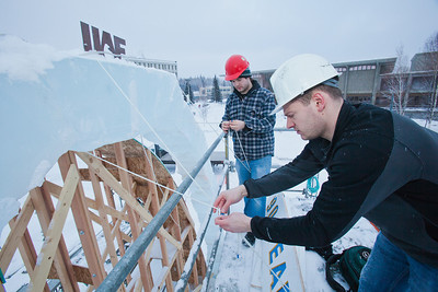 """Engineering students Sam Carlson, left, and Andy Chamberlain climb scaffolding to hang a sign reading """"90 Years of Engieering"""" from the apex of the 2012 ice arch in front of the Duckering Building on the Fairbanks campus.  Filename: AAR-12-3298-09.jpg"""