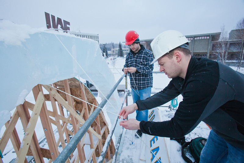 """Engineering students Sam Carlson, left, and Andy Chamberlain climb scaffolding to hang a sign reading """"90 Years of Engieering"""" from the apex of the 2012 ice arch in front of the Duckering Building on the Fairbanks campus.  <div class=""""ss-paypal-button"""">Filename: AAR-12-3298-09.jpg</div><div class=""""ss-paypal-button-end"""" style=""""""""></div>"""