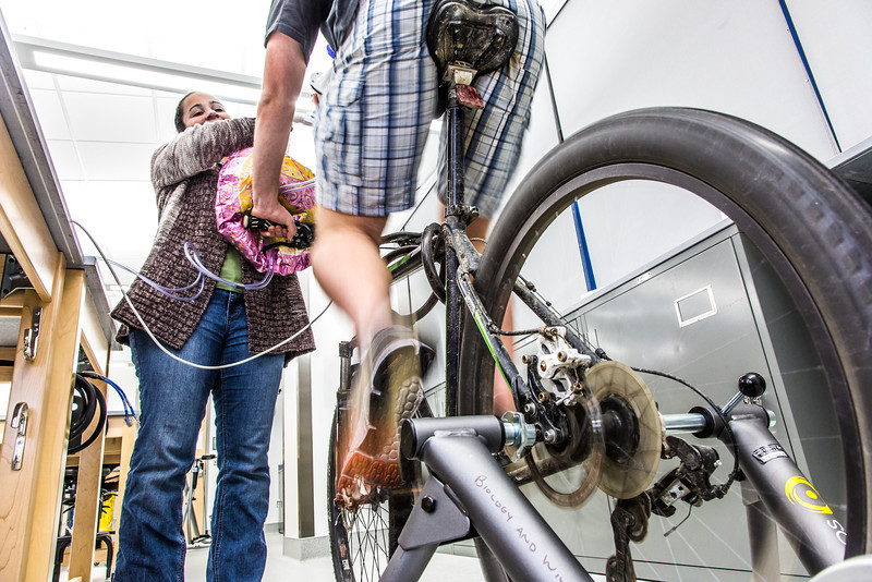 """Ivan Lien works out on his bicycle while Marisol Bastiani helps collect data measuring his respiration during a human physiology lab in the Murie Building.  <div class=""""ss-paypal-button"""">Filename: AAR-13-3983-70.jpg</div><div class=""""ss-paypal-button-end"""" style=""""""""></div>"""