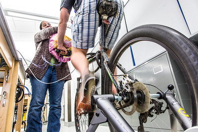 Ivan Lien works out on his bicycle while Marisol Bastiani helps collect data measuring his respiration during a human physiology lab in the Murie Building.  Filename: AAR-13-3983-70.jpg