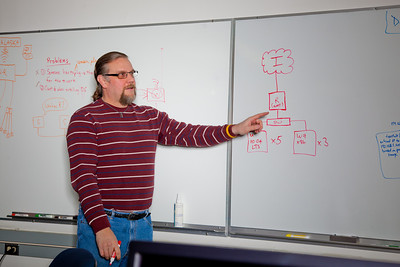 Computer Science Associate Professor Jon Genetti points to a diagram during a class in the Chapman Building ASSERT lab.  Filename: AAR-12-3272-42.jpg