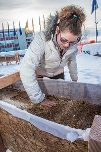 Civil engineering major Katrina Monta levels out sawdust mixed with water that when frozen, hardens into a substance many times stronger than concrete. Katrina and others are hard at work on this year's ice arch, scheduled for completion Feb. 20.  Filename: AAR-13-3718-23.jpg
