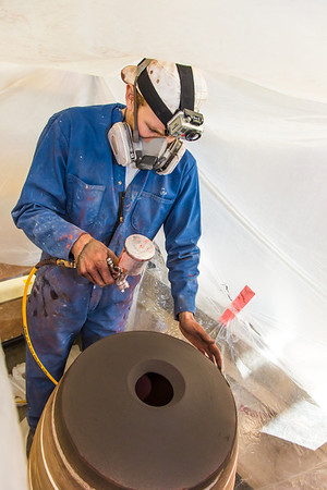 Art major Ian Wilkinson applies glaze from an airbrush under a temporary visqueen tent set up in the ceramics studio. The large pot is part of his BFA thesis project which opens next week in the UAF Fine Arts gallery.  Filename: AAR-13-3768-24.jpg