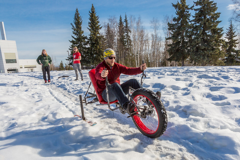 """Mechanical engineering majors Daniel Sandstrom, left, Eric Bookless and Neil Gotschall, front, demonstrate their fat tire ski bike they designed and built for paraplegic users as their spring 2016 senior design project. The bike is powered by pushing and pulling on the handles.  <div class=""""ss-paypal-button"""">Filename: AAR-16-4856-06.jpg</div><div class=""""ss-paypal-button-end""""></div>"""