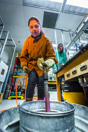 Research Assistant Professor Jessica Larsen, at right, operates the valve while volcanology graduate student Rebecca deGraffenreid uses water to cool down a rod which contains volcanic remnants after it was pulled from a furnace in the Reichardt Building petrology lab.  Filename: AAR-16-4828-101.jpg