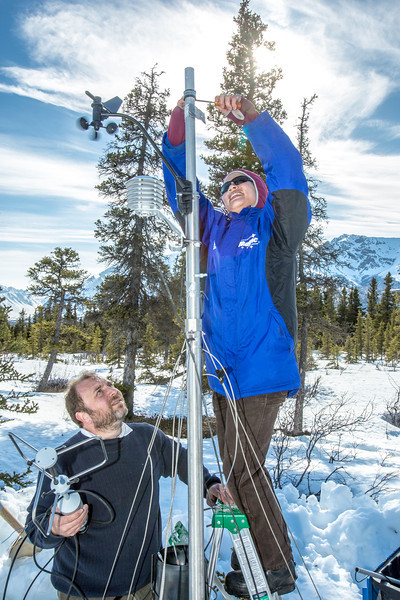 """Research associate professor Javier Fochesatto, left, watches as Daisy Huang, a research engineer for the Alaska Center for Energy and Power secures components on a remote meteorological station on a hillside near the Black Rapids Lodge, about 150 miles southeast of Fairbanks. The station will record wind speed and direction, as well as temperatures at different altitudes.  <div class=""""ss-paypal-button"""">Filename: AAR-13-3843-195.jpg</div><div class=""""ss-paypal-button-end"""" style=""""""""></div>"""