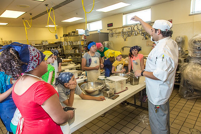 Luis Martinez, right, program manager for CTC's Culinary Arts program, leads the UAF Summer Session's Baking Blitz for local elementary school kids May 28 in the Hutchison kitchen.  Filename: AAR-14-4203-25.jpg