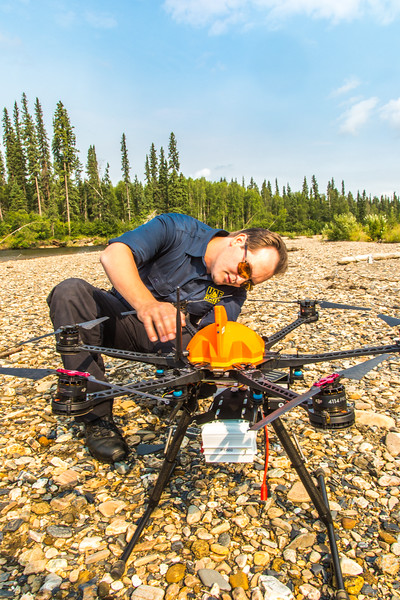 """Trevor Parcell with the Alaska Center for Unmanned Aircraft Systems Integration (ACUASI) sets up a piloting station on a gravel bar along the upper Chena River. The UAV pilot was taking part in a joint effort with the U.S. Fish and Wildlife Service to collect video of important king salmon spawning habitat.  <div class=""""ss-paypal-button"""">Filename: AAR-15-4593-097.jpg</div><div class=""""ss-paypal-button-end""""></div>"""