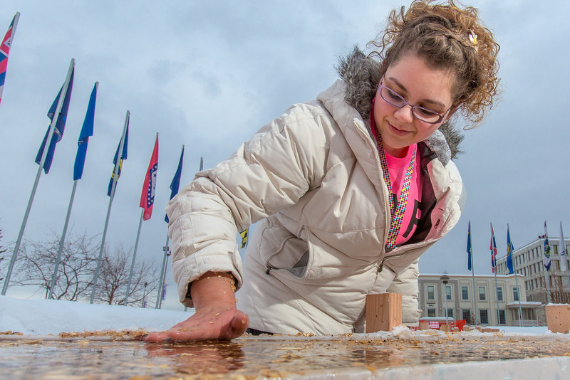 """Civil engineering major Katrina Monta smooths the surface of a combination of sawdust and water that when frozen, hardens into a substance many times stronger than concrete. Katrina and others are hard at work on this year's traditional ice arch, designed and built each year by engineering students.  <div class=""""ss-paypal-button"""">Filename: AAR-13-3727-39.jpg</div><div class=""""ss-paypal-button-end"""" style=""""""""></div>"""