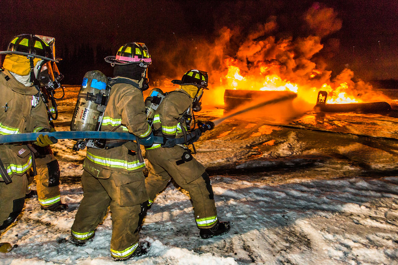 """Student firefighters with the University Fire Department spray water on a blaze of burning fuel during a live training drill at the Fairbanks International Airport.  <div class=""""ss-paypal-button"""">Filename: AAR-13-3995-167.jpg</div><div class=""""ss-paypal-button-end"""" style=""""""""></div>"""
