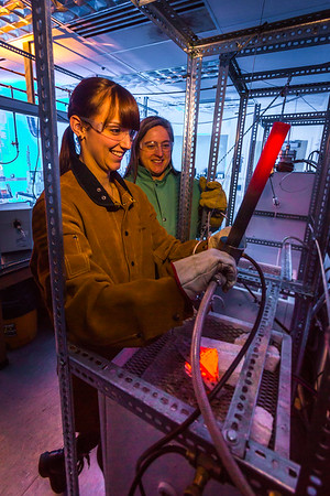 Ph.D. candidate Amanda Lindoo pulls a rod containing volcanic remnants from a furnace in the Reichardt Building petrology lab under the watchful gaze of Research Assistant Professor Jessica Larsen.  Filename: AAR-16-4828-063.jpg