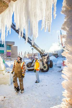 Volunteers from GHEMM, Inc. use a crane to lift the buttresses for this year's student-built ice arch into position in Cornerstone Plaza on campus. The annual ice arch is designed and built by a team of engineering students, a UAF tradition going back more than 60 years.  Filename: AAR-14-4078-15.jpg