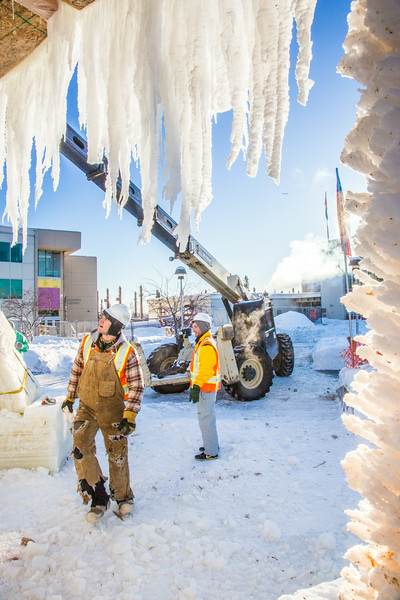 """Volunteers from GHEMM, Inc. use a crane to lift the buttresses for this year's student-built ice arch into position in Cornerstone Plaza on campus. The annual ice arch is designed and built by a team of engineering students, a UAF tradition going back more than 60 years.  <div class=""""ss-paypal-button"""">Filename: AAR-14-4078-15.jpg</div><div class=""""ss-paypal-button-end""""></div>"""