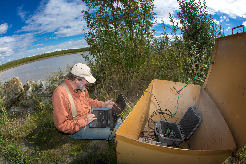 """Jack Schmid, a research professionals with the Alaska Center for Energy and Power, enters data at a remote recording station set up on the banks of the Tanana River near Nenana. Schmid is part of a team conducting research on the feasibility of using the river current to generate electricity for potential use throughout rural Alaska.  <div class=""""ss-paypal-button"""">Filename: AAR-12-3500-181.jpg</div><div class=""""ss-paypal-button-end"""" style=""""""""></div>"""