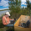 "Jack Schmid, a research professionals with the Alaska Center for Energy and Power, enters data at a remote recording station set up on the banks of the Tanana River near Nenana. Schmid is part of a team conducting research on the feasibility of using the river current to generate electricity for potential use throughout rural Alaska.  <div class=""ss-paypal-button"">Filename: AAR-12-3500-181.jpg</div><div class=""ss-paypal-button-end"" style=""""></div>"