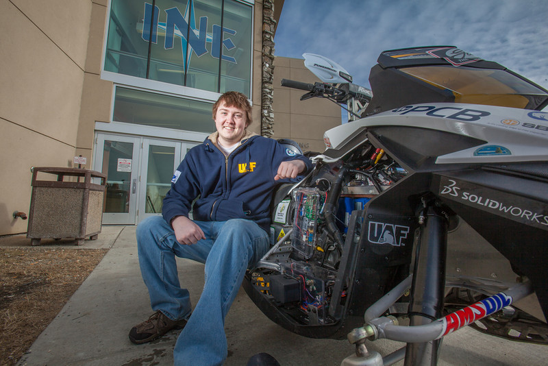"""Mechanical enineering major Ben Neubauer poses with the UAF team's snowmobile in front of the Duckering Building after its return from competing in the Society of Automotive Engineers' Clean Snowmobile Challenge in Houghton, Mich.  <div class=""""ss-paypal-button"""">Filename: AAR-12-3345-100.jpg</div><div class=""""ss-paypal-button-end"""" style=""""""""></div>"""
