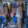 "Associate professor Wendy Croskrey, left, and student volunteers help transport a pot of molten bronze to the molds for pouring as part of Joel Isaak's senior thesis project.  <div class=""ss-paypal-button"">Filename: AAR-12-3347-080.jpg</div><div class=""ss-paypal-button-end"" style=""""></div>"