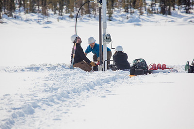 Associate Professor Mat Wooller, blue shirt, and Ph.D. candidate Jim Shobe, left, test a new vibra-coring system through a hole in lake ice to sample long cores of sediment deep below the lake's bottom. Also helping is Terry Smith, right, a North Pole High School student intern.  Filename: AAR-12-3346-023.jpg