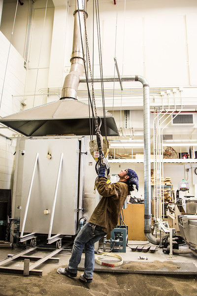 """Art major Joel Isaak positions equipment prior to pouring molten bronze as part of the process of creating a life-sized sculpture for his senior thesis in the UAF Fine Arts complex.  <div class=""""ss-paypal-button"""">Filename: AAR-12-3347-003.jpg</div><div class=""""ss-paypal-button-end"""" style=""""""""></div>"""