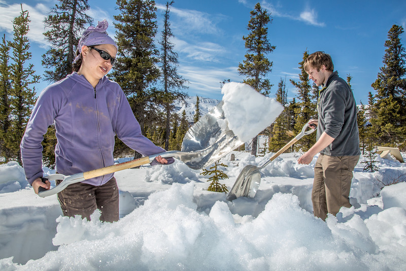 """Daisy Huang, a research engineer for the Alaska Center for Energy and Power, works with intern Luke George to clear snow needed to install a SODAR station on a hillside near the Black Rapids Lodge, about 150 miles southeast of Fairbanks. The station uses sound waves to measure atmospheric distrubances to produce a profile of wind speed and direction at a range of altitudes.  <div class=""""ss-paypal-button"""">Filename: AAR-13-3843-59.jpg</div><div class=""""ss-paypal-button-end"""" style=""""""""></div>"""