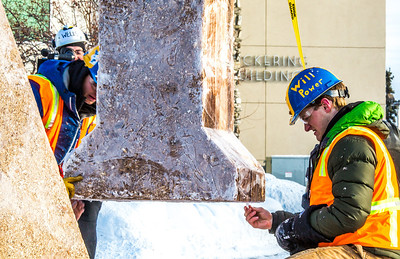 Engineering students clear the bottom of one of the vertical supports as they raise the 2013 ice arch in Cornerstone Plaza on the Fairbanks campus. Students this year built the structure out of a mixture of ice and sawdust, which is many times stronger than concrete.  Filename: AAR-13-3736-114.jpg