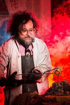 Geology professor Rainer Newberry pours hot lava over volcanic basalt during a set-up photoshoot in a Reichardt Building lab in on the Fairbanks campus.  Filename: AAR-13-3732-35.jpg