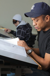 Anthony Rogers reads through the textbook in his drafting class in UAF's Community and Technical College.  Filename: AAR-11-3221-50.jpg