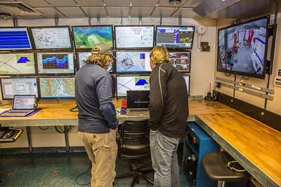 Dan Oliver, left, marine superintendent, and Steve Hartz, science support lead on the R/V Sikuliaq, keep track of activity on various computer monitors from a lab off the main deck as the ship sits at the dock in Juneau during a stopover on its inaugural voyage to its home port of Seward in Feb., 2015.  Filename: AAR-15-4456-087.jpg