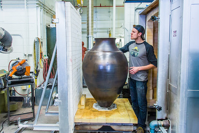 Art major Ian Wilkinson inspects one of his ceramic pieces as it emerges from the kiln. The large pot is part of his BFA thesis project which opens next week in the UAF Fine Arts gallery.  Filename: AAR-13-3768-40.jpg