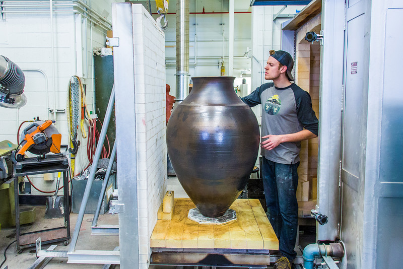 """Art major Ian Wilkinson inspects one of his ceramic pieces as it emerges from the kiln. The large pot is part of his BFA thesis project which opens next week in the UAF Fine Arts gallery.  <div class=""""ss-paypal-button"""">Filename: AAR-13-3768-40.jpg</div><div class=""""ss-paypal-button-end"""" style=""""""""></div>"""