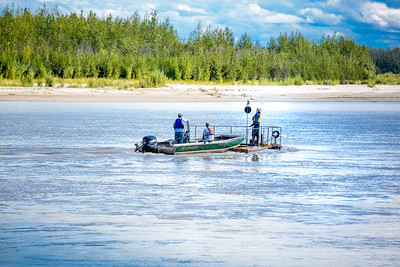 Researchers with UAF's School of Fisheries and Ocean Sciences and the Alaska Center for Energy and Power (ACEP) check equipment on a prototype deployment boom on a barge anchored in the Tanana River near Nenana. They're part of a team conducting research on the feasibility of using the river current  to generate electricity for potential use throughout rural Alaska.  Filename: AAR-12-3500-216.jpg