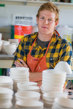 Art major Ian Wilkinson poses with a few of the approximately 1,000 ceramic bowls needed for his senior thesis project in the fine arts complex on the Fairbanks campus.  Filename: AAR-12-3547-103.jpg