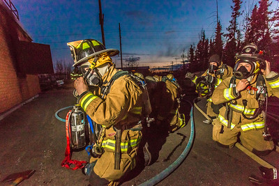 Student firefighters don their masks before entering a burning building as part of a UFD live training drill at the Fairbanks Fire Training Center.  Filename: AAR-13-3978-36.jpg
