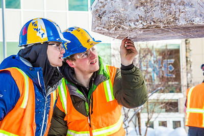 Engineering students clear the bottom of one of the vertical supports as they raise the 2013 ice arch in Cornerstone Plaza on the Fairbanks campus. Students this year built the structure out of a mixture of ice and sawdust, which is many times stronger than concrete.  Filename: AAR-13-3736-128.jpg