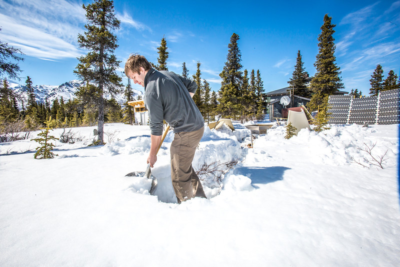 "Luke George, a senior mechanical engineering major at UAF, digs a path in the deep snow near Black Rapids Lodge about 150 miles southeast of Fairbanks. George, a summer intern for the Alaska Center for Energy and Power, was helping to install a SODAR station which uses sound waves to measure atmospheric distrubances to produce a profile of wind speed and direction at a range of altitudes.  <div class=""ss-paypal-button"">Filename: AAR-13-3843-29.jpg</div><div class=""ss-paypal-button-end"" style=""""></div>"