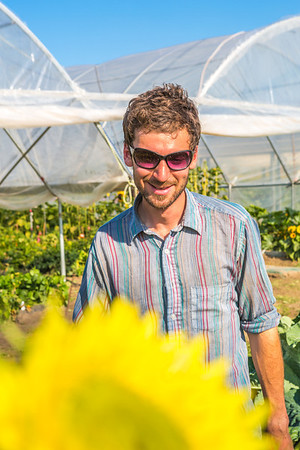 Cameron Willingham, a research technician for UAF's School of Natural Resources and Agricultural Sciences, helps keep the research garden looking great during its late-summer glory.  Filename: AAR-12-3494-49.jpg