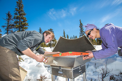 Daisy Huang, a research engineer for the Alaska Center for Energy and Power, works with intern Luke George to level a SODAR station on a hillside near the Black Rapids Lodge. The station uses sound waves to measure atmospheric distrubances to produce a profile of wind speed and direction at a range of altitudes.  Filename: AAR-13-3843-9.jpg
