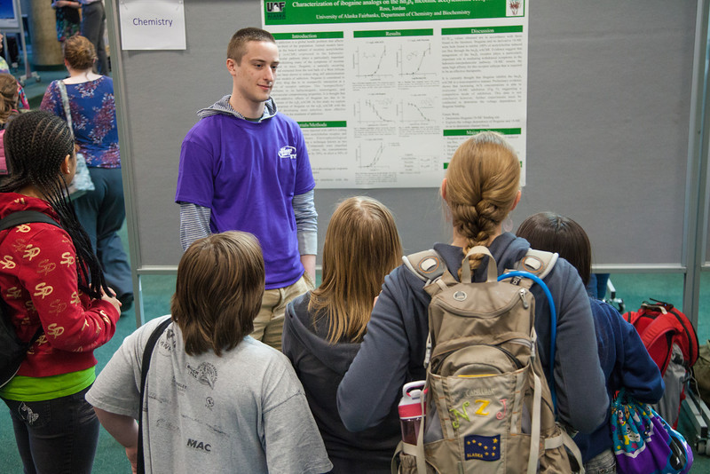 "Chemistry major Jordan Ross describes his poster to a group of Fairbanks elementary students during the Research Day poster session in the Wood Center.  <div class=""ss-paypal-button"">Filename: AAR-12-3363-11.jpg</div><div class=""ss-paypal-button-end"" style=""""></div>"