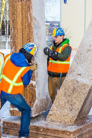 Engineering students help stabilize one of the vertical supports as they raise the 2013 ice arch in Cornerstone Plaza on the Fairbanks campus. Students this year built the structure out of a mixture of ice and sawdust, which is many times stronger than concrete.  Filename: AAR-13-3736-84.jpg