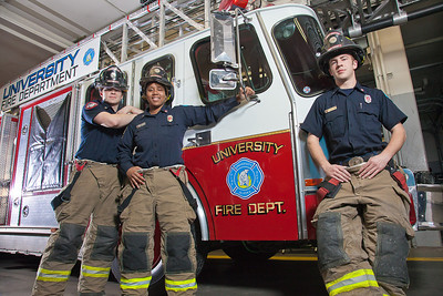 UAF student firefighters/EMTs John McGee, left, Lillian Hampton and Ethan Stevenson pose by one of the firetrucks housed in the Whitaker Building on the Fairbanks campus.  Filename: AAR-11-3223-102.jpg
