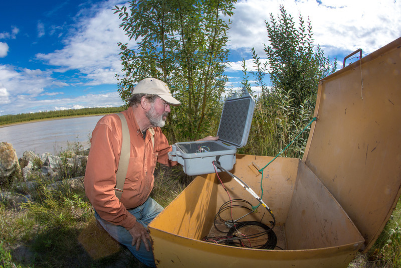 """Jack Schmid, a research professionals with the Alaska Center for Energy and Power, prepares to enter data at a remote recording station set up on the banks of the Tanana River near Nenana. Schmid is part of a team conducting research on the feasibility of using the river current to generate electricity for potential use throughout rural Alaska.  <div class=""""ss-paypal-button"""">Filename: AAR-12-3500-175.jpg</div><div class=""""ss-paypal-button-end"""" style=""""""""></div>"""