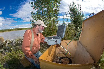 Jack Schmid, a research professionals with the Alaska Center for Energy and Power, prepares to enter data at a remote recording station set up on the banks of the Tanana River near Nenana. Schmid is part of a team conducting research on the feasibility of using the river current to generate electricity for potential use throughout rural Alaska.  Filename: AAR-12-3500-175.jpg