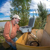 "Jack Schmid, a research professionals with the Alaska Center for Energy and Power, prepares to enter data at a remote recording station set up on the banks of the Tanana River near Nenana. Schmid is part of a team conducting research on the feasibility of using the river current to generate electricity for potential use throughout rural Alaska.  <div class=""ss-paypal-button"">Filename: AAR-12-3500-175.jpg</div><div class=""ss-paypal-button-end"" style=""""></div>"