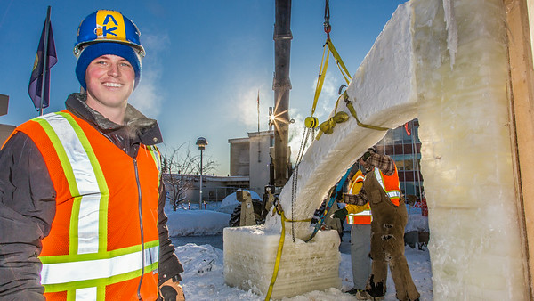 Tripp Collier, one of the project managers for this year's student ice arch, works woth other students and a volunteer from GHEMM Co., to raise the first of four buttresses used in the creative design.  Filename: AAR-14-4078-26.jpg