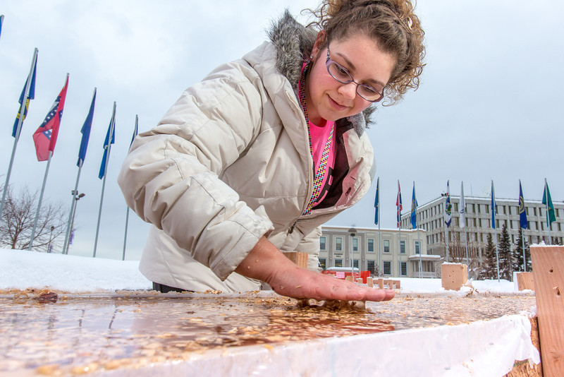 """Civil engineering major Katrina Monta smooths the surface of a combination of sawdust and water that when frozen, hardens into a substance many times stronger than concrete. Katrina and others are hard at work on this year's traditional ice arch, designed and built each year by engineering students.  <div class=""""ss-paypal-button"""">Filename: AAR-13-3727-37.jpg</div><div class=""""ss-paypal-button-end"""" style=""""""""></div>"""