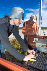 Paul Duvoy, front, and Jack Schmid, research professionals with the Alaska Center for Energy and Power, enter data into a remote recording station set up on the banks of the Tanana River near Nenana. The pair are part of a team conducting research on the feasibility of using the river current to generate electricity for potential use throughout rural Alaska.  Filename: AAR-12-3500-156.jpg