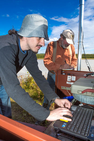 """Paul Duvoy, front, and Jack Schmid, research professionals with the Alaska Center for Energy and Power, enter data into a remote recording station set up on the banks of the Tanana River near Nenana. The pair are part of a team conducting research on the feasibility of using the river current to generate electricity for potential use throughout rural Alaska.  <div class=""""ss-paypal-button"""">Filename: AAR-12-3500-156.jpg</div><div class=""""ss-paypal-button-end"""" style=""""""""></div>"""