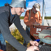 "Paul Duvoy, front, and Jack Schmid, research professionals with the Alaska Center for Energy and Power, enter data into a remote recording station set up on the banks of the Tanana River near Nenana. The pair are part of a team conducting research on the feasibility of using the river current to generate electricity for potential use throughout rural Alaska.  <div class=""ss-paypal-button"">Filename: AAR-12-3500-156.jpg</div><div class=""ss-paypal-button-end"" style=""""></div>"