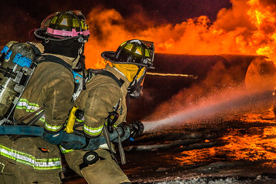 Student firefighters with the University Fire Department spray water on a blaze of burning fuel during a live training drill at the Fairbanks International Airport.  Filename: AAR-13-3995-193.jpg
