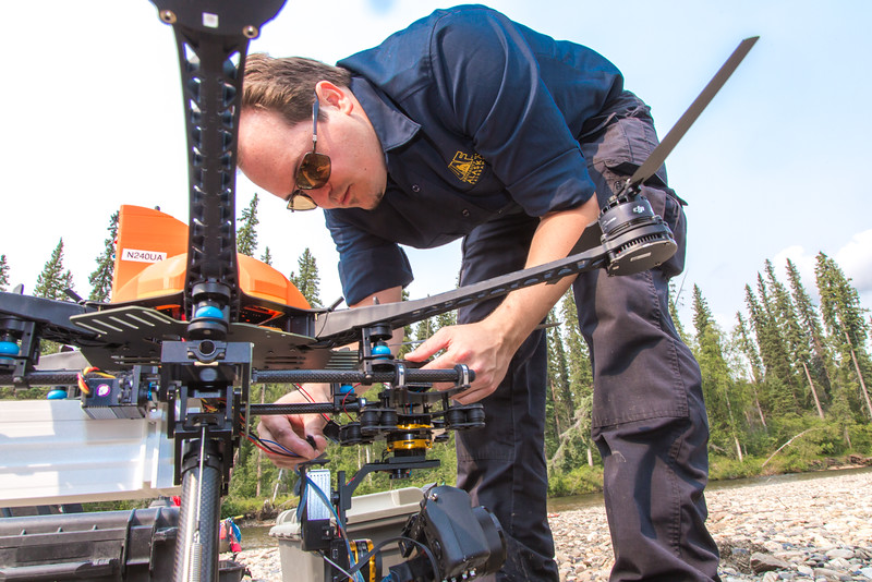 """Trevor Parcell with the Alaska Center for Unmanned Aircraft Systems Integration (ACUASI) sets up a piloting station on a gravel bar along the upper Chena River. The UAV pilot was taking part in a joint effort with the U.S. Fish and Wildlife Service to collect video of important king salmon spawning habitat.  <div class=""""ss-paypal-button"""">Filename: AAR-15-4593-155.jpg</div><div class=""""ss-paypal-button-end""""></div>"""